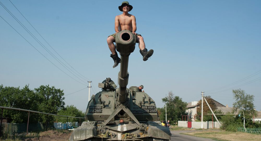 Ukrainian soldier sits atop of a self-propelled gun as an army column of military vehicles prepares to roll to a frontline near Illovaisk, Donetsk region, eastern Ukraine