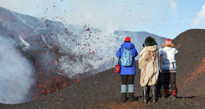 Women photograph a side breakthrough eruption of Plosky Tobalchik volcano in Kamchatka