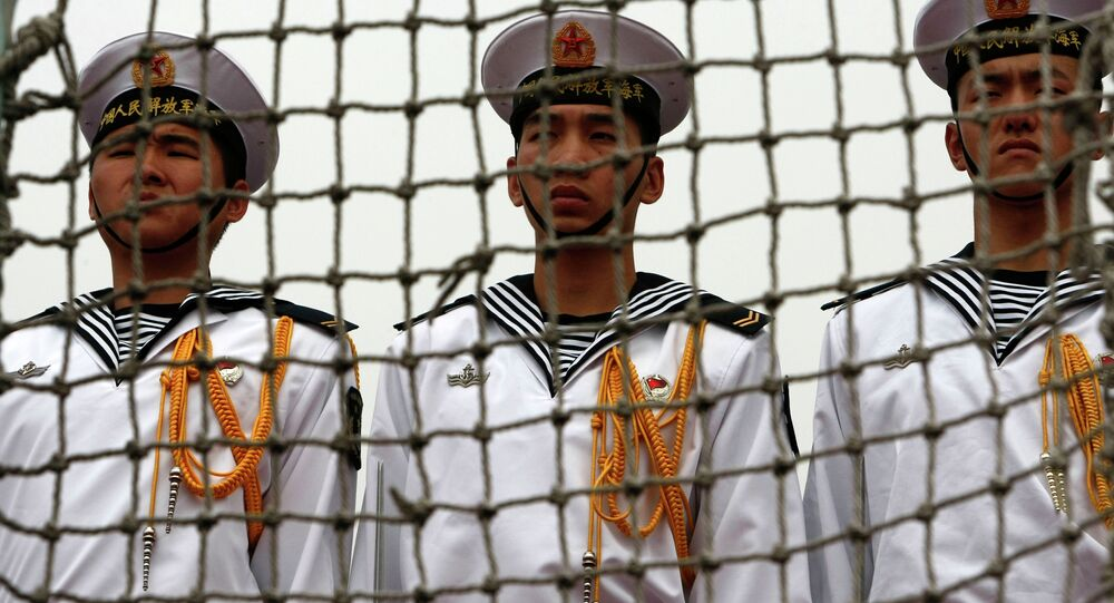 Chinese Navy seamen stand at attention on the deck of the Chinese missile frigate Ma'anshan, the flagship of the Chinese People's Liberation Army Navy Task Force 525