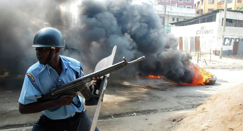 A riot police officer near to a tire on fire, lit by Muslim youths, outside Masjid Musa Mosque, in Majengo, Mombasa, Kenya