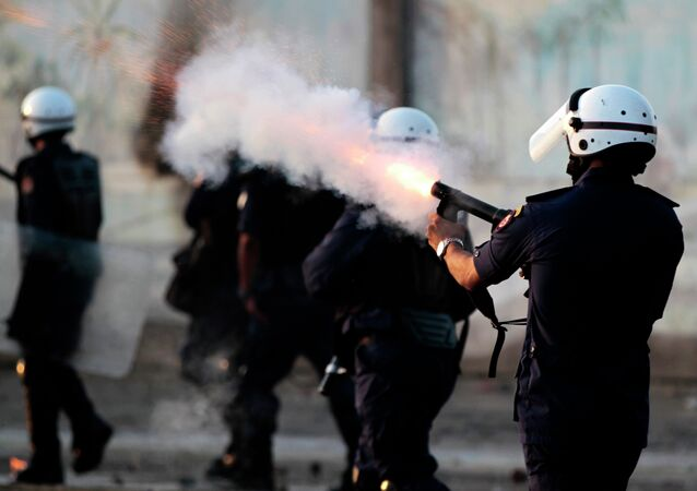Riot police fire tear gas as they chase Bahraini anti-government protesters throwing stones and petrol bombs on the outskirts of the capital of Manama, Bahrain