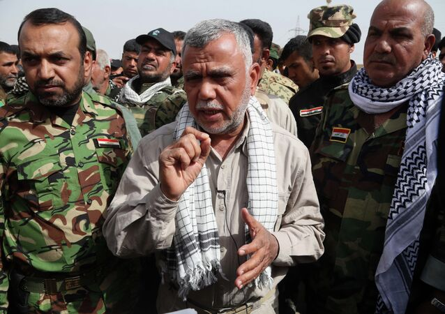 Hadi al-Amiri commander, center, of Iraq's powerful Shiite militias speaks during an interview with The Associated Press on the battlefield near the Iraqi city of Tikrit, 80 miles (130 kilometers) north of Baghdad, Iraq, Friday, March 13, 2015. Al-Amiri accused the U.S. of falling short on promises to help Iraq in its battle against the Islamic State group and called Iranian assistance to Iraqi security forces unconditional.