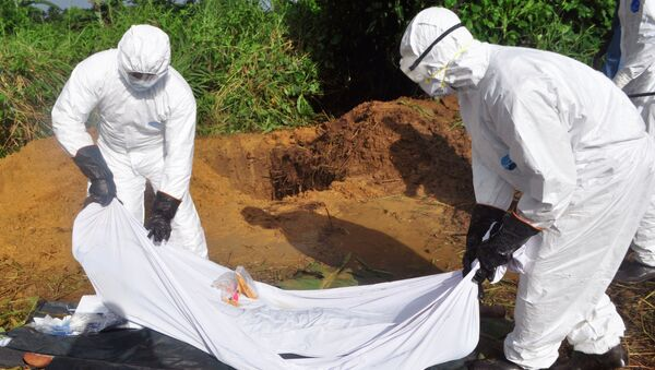 Health workers prepare to place the body of a man who was suspected of dying from the Ebola virus into a grave on the outskirts of Monrovia, Liberia - Sputnik International