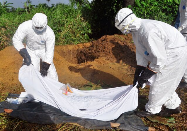 Health workers prepare to place the body of a man who was suspected of dying from the Ebola virus into a grave on the outskirts of Monrovia, Liberia