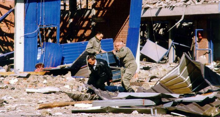 Workers clean the debris of a police training centre in Novi Sad, in the north of Yugoslavia 25 March 1999 which was destroyed during NATO air strikes, according to the official Yugoslav news agency, Tanjug.