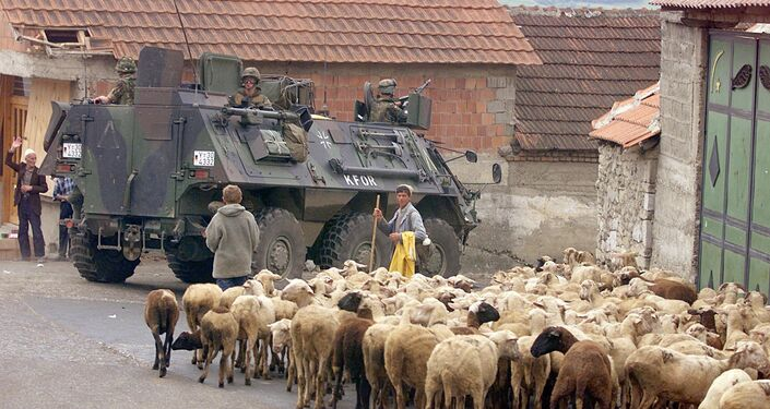 A German armoured vehicle part of the NATO-led KFOR troops drives past a herd of sheep 17 June 1999 in Orahovac, south western Kosovo.