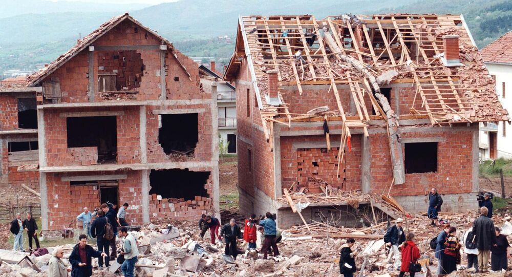 Serb civilians and reporters walk around a residential area damaged during a NATO attack on a neighboring army compound (300 kilometers south of Belgrade), Wednesday, April 28, 1999.