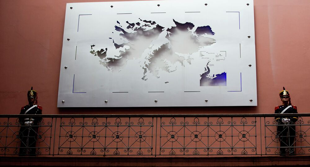 Soldiers stand next to a map of the Falkland Islands
