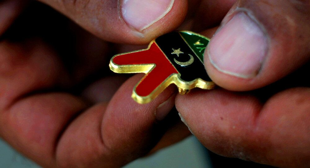 A Libyan man holds a souvenir of the Libyan revolution in the colors of the pre-Gadhafi flag
