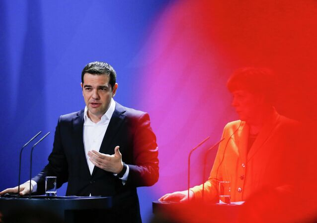 In this photo taken with a red television camera control light in the foreground, German Chancellor Angela Merkel, right, and the Prime Minister of Greece Alexis Tsipras