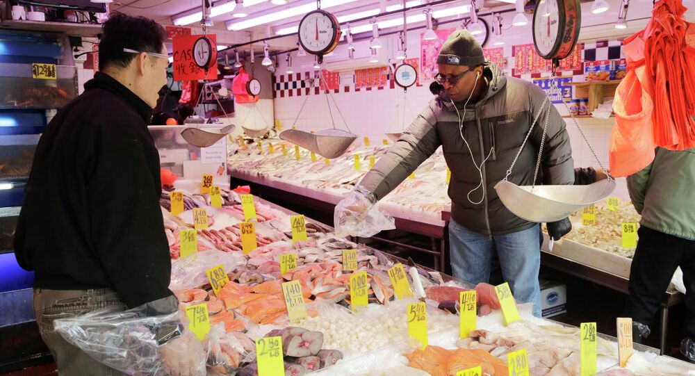 A customer selects seafood at Hung Kee Fish & Meat Food Market in New York.