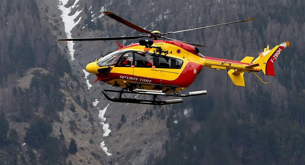 A helicopter of the French civil security services flies in French Alps