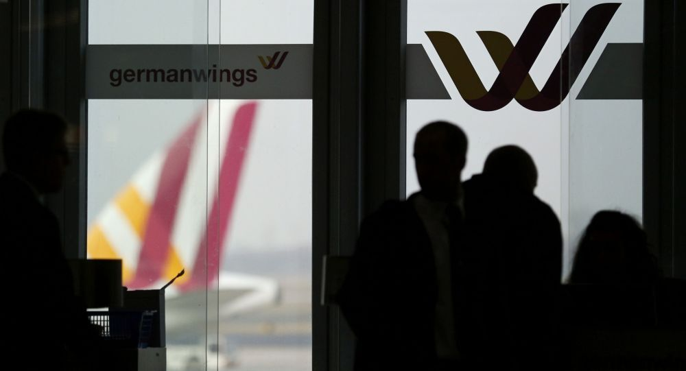 Passengers are silhouetted against a window at the Germanwings check-in desk at Dusseldorf airport March 24, 2015.
