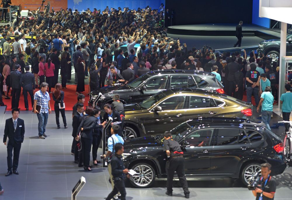People look at cars displayed at the 36th Bangkok International Motor Show on March 24, 2015