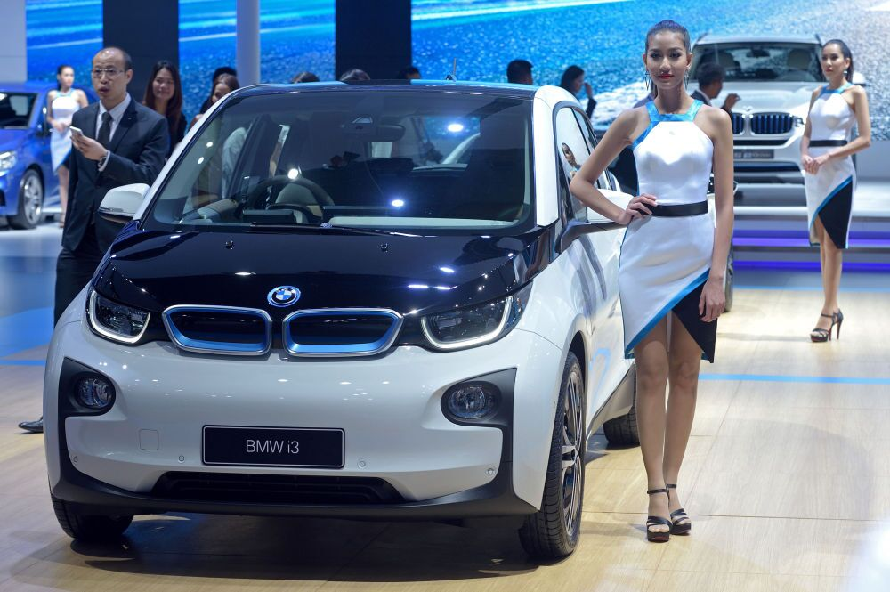 A model poses next to the new BMW i3 displayed at the 36th Bangkok International Motor Show on March 24, 2015
