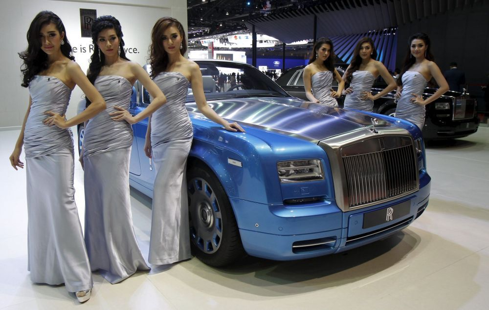 Models pose beside a Rolls-Royce Phantom Drophead Coupe Waterspeed during a media presentation of the 36th Bangkok International Motor Show in Bangkok March 24, 2015