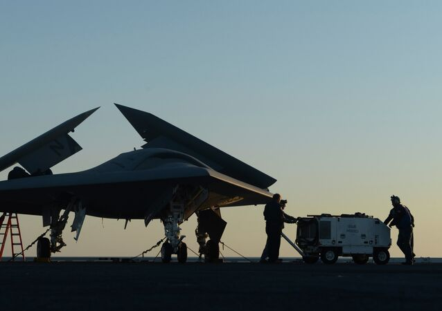 Sailors working on an X-47B Unmanned Combat Air System (UCAS) at dawn aboard the aircraft carrier USS George H.W. Bush