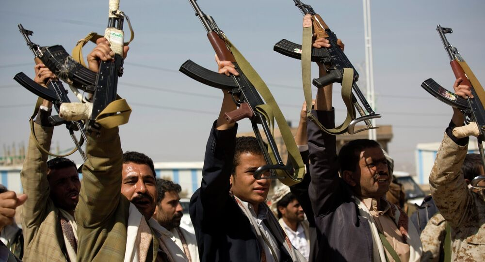 Houthi Shiite Yemeni raise their weapons