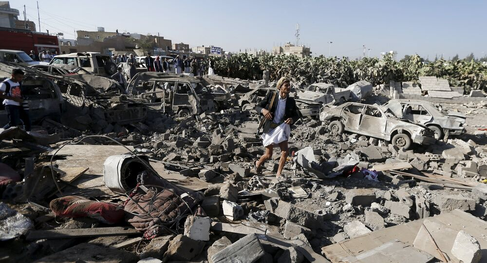 An armed man walks on the rubble of houses destroyed by an air strike near Sanaa Airport March 26, 2015.