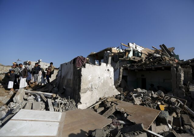 People gather at the site of an air strike at a residential area near Sanaa Airport March 26, 2015.