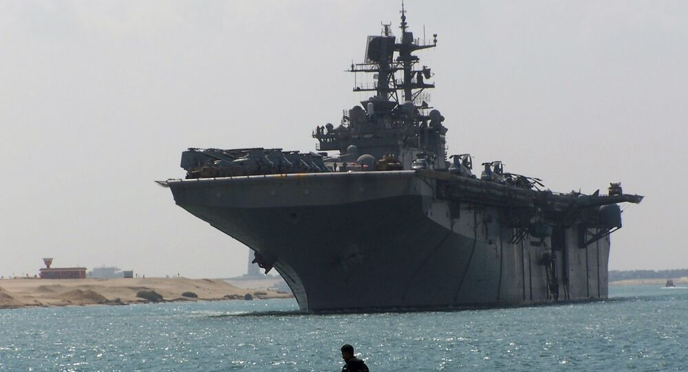 Egyptian men look at the multipurpose amphibious assault ship USS Iwo Jima (LHD 7) as it transits through the Suez Canal.