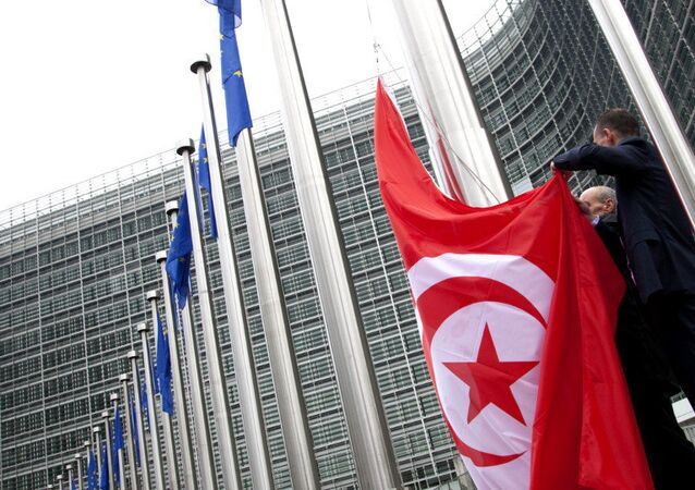 Officials prepare to put up the Tunisian flag in front of EU headquarters