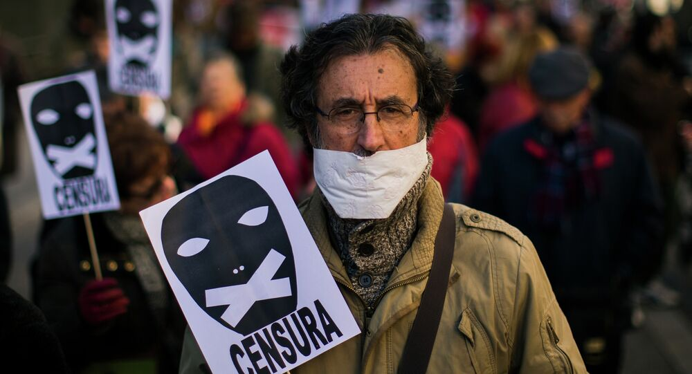 A demonstrator marches with his mouth covered and carries a placard that reads: Censorship during a protest against Spanish Citizens Security Law in Madrid