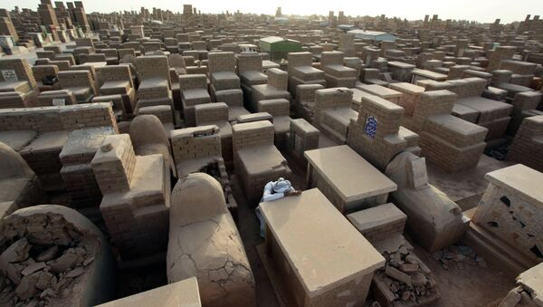 Mushtaq Wahab slumps by the grave of his son, who was killed in a bombing in Baghdad in 2009. - Sputnik International