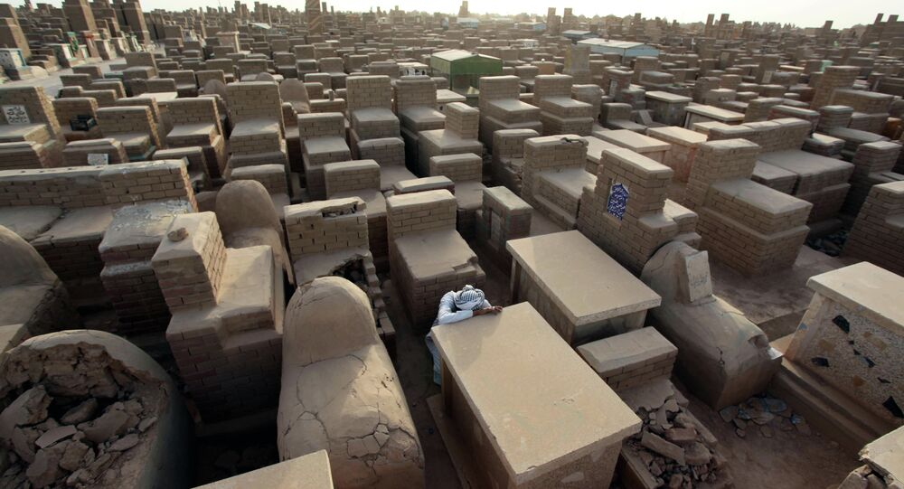Mushtaq Wahab slumps by the grave of his son, who was killed in a bombing in Baghdad in 2009.