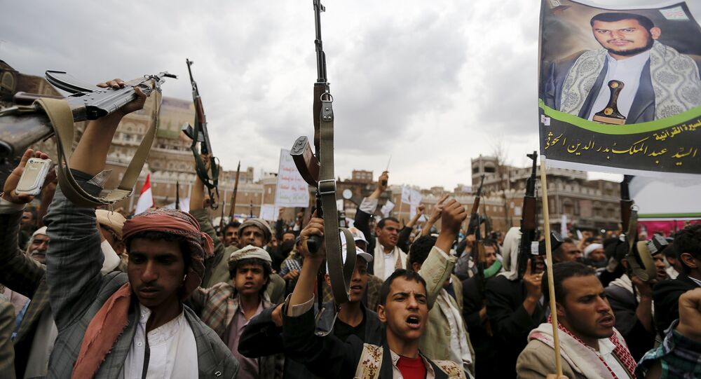 Shi'ite Muslim rebels hold up their weapons during a rally against air strikes in Sanaa March 26, 2015