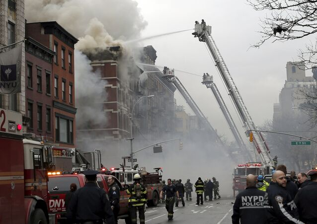 New York City Fire Department and Police stand by as firefighters fight a fire near where a residential apartment building collapsed and was engulfed in flames in New York City's East Village neighborhood