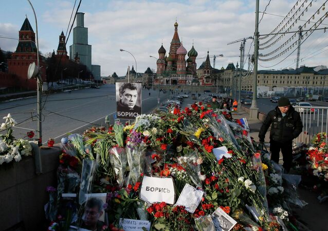 A man walks past flowers at the site where Kremlin critic Boris Nemtsov was murdered on February 27, at the Great Moskvoretsky Bridge, with St. Basil's Cathedral seen in the background, in central Moscow March 6, 2015
