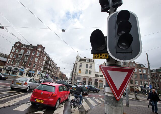 Cars and bicycles improvise crossing an intersection as traffic lights are off during a power outage in Amsterdam, Netherlands, Friday, March 27, 2015.