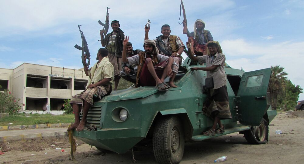 Militiamen loyal to President Abed Rabbo Mansour Hadi ride on an army vehicle on a street in Aden, Yemen