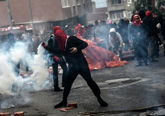 A man throws gas canister back to Turkish riot policemen, on March 11, 2015