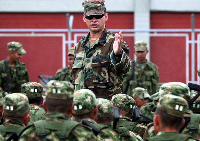 Colombian soldiers listen to an unidentified U.S. Special Forces trainer at a military base in Pueblo Tapao, northwestern Colombia, Friday, May 4, 2007