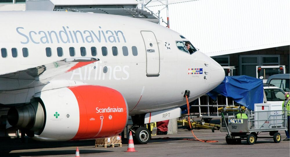 The pilot of an SAS Boeing 737 series jet speaks to his ground staff through the cockpit window at the gate of Terminal 4 at Arlanda Airport in Stockholm, Sweden. File photo