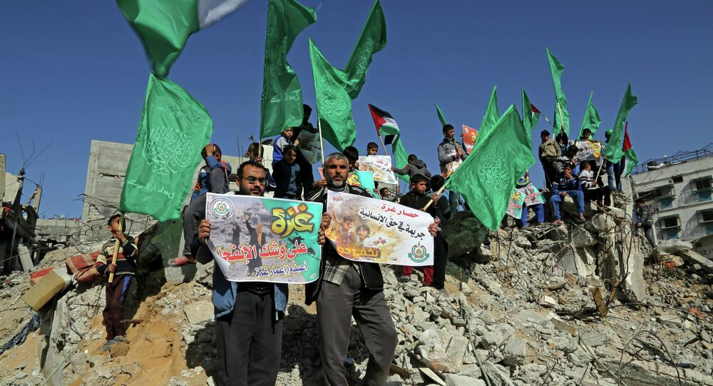 Palestinian Hamas supporters wave Hamas flags during a protest against the decision by the U.N. Relief and Works Agency to suspended an aid program for Gaza residents displaced by the last summer's war, in Beit Hanoun, northern Gaza. File photo