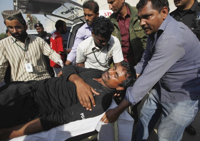 Men move an injured Special Service Unit (SSU) soldier outside a hospital, after he was wounded with others from an explosion near their vehicle, in Karachi