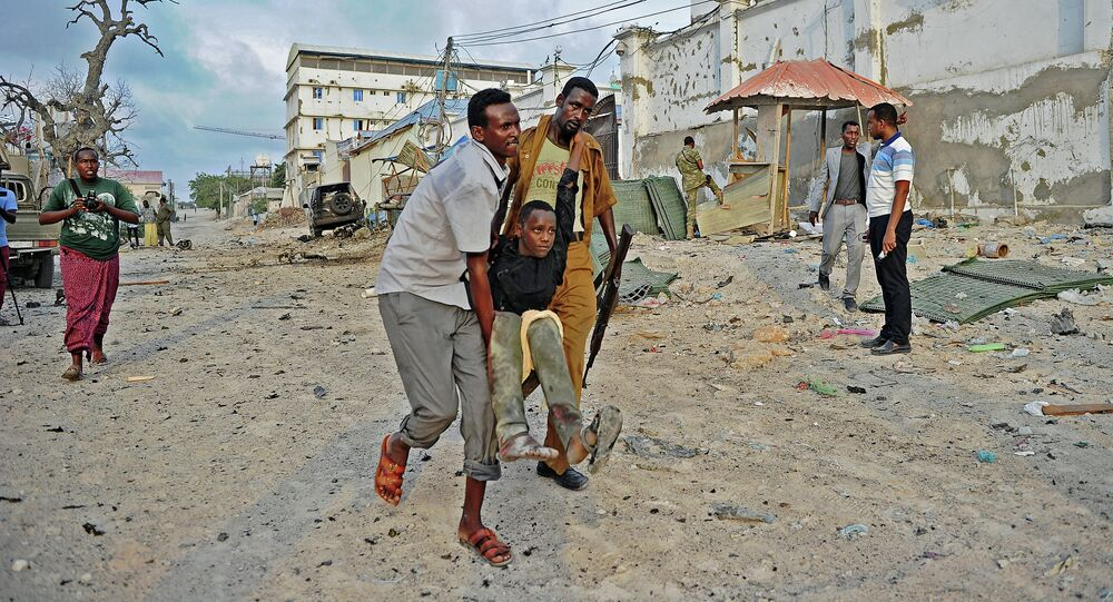 An injured youth is carried away from the scene of a car bomb attack and armed raid by Al Shebab militants on the Maka al Mukarama hotel in Mogadishu on March 27, 2015