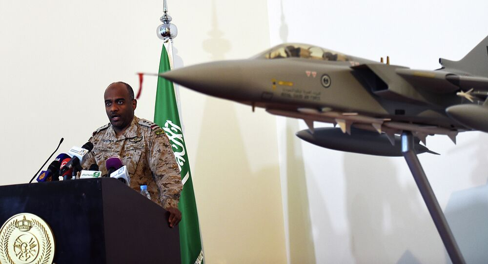 Saudi Brigadier General Ahmed Asiri, spokesman of the Saudi-led coalition forces, speaks to the media next to a replica of a Tornado fighter jet, at the Riyadh airbase in the Saudi capital on March 26, 2014