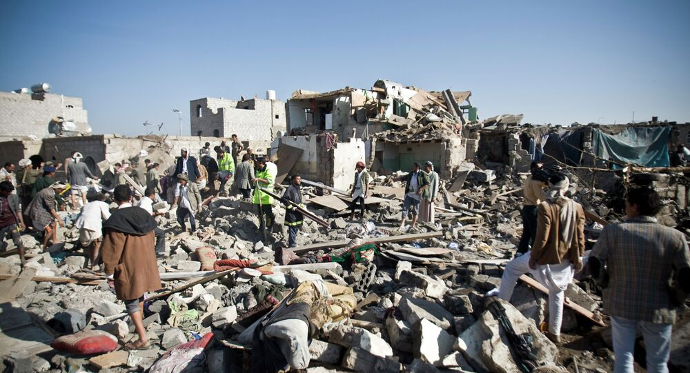 People search for survivors under the rubble of houses destroyed by Saudi airstrikes near Sanaa Airport, Yemen