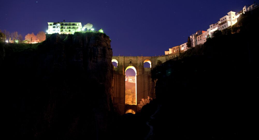 The New Bridge of Ronda is enlightened from behind during the global climate change awareness campaign Earth Hour, on March 28, 2015