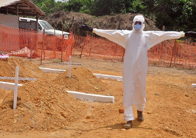 A health worker holds up his arms after he and others buried a person that they suspect died form the Ebola virus at a new graveyard on the outskirts of Monrovia, Liberia