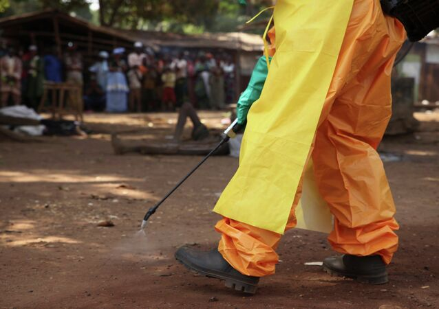 A member of the French Red Cross disinfects the area around a motionless person suspected of carrying the Ebola virus as a crowd gathers in Forecariah, Guinea