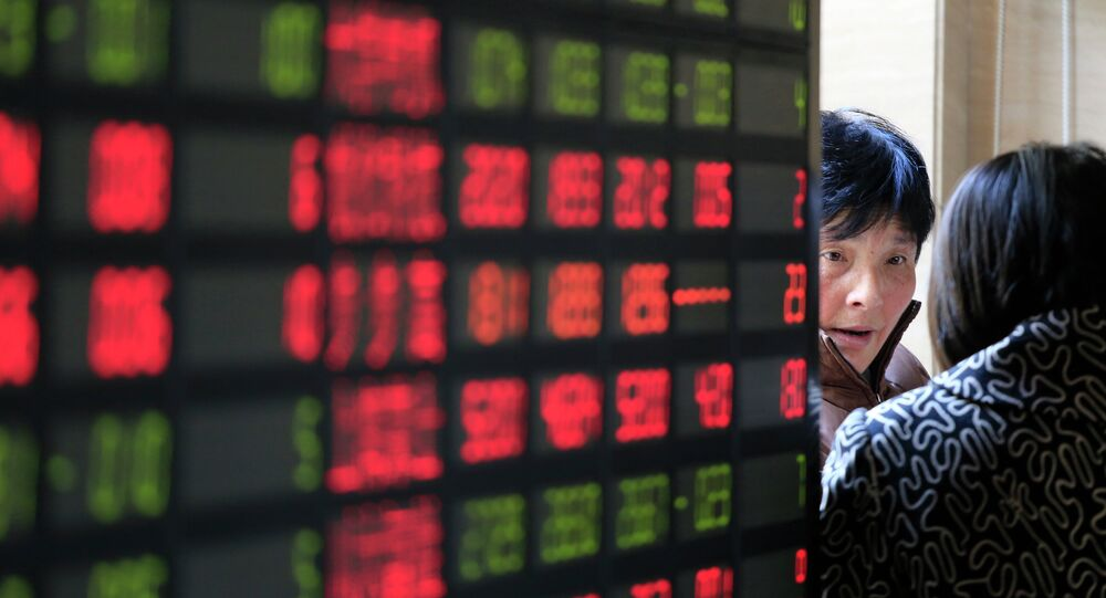 Investors talk next to the stock price monitor at a private securities company Thursday Dec. 19, 2013 in Shanghai, China
