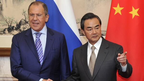 Russian Foreign Minister Sergey Lavrov (L) shakes hands with Chinese Foreign Minister Wang Yi before their meeting at Diaoyutai Guesthouse in Beijing on April 15, 2014 - Sputnik International