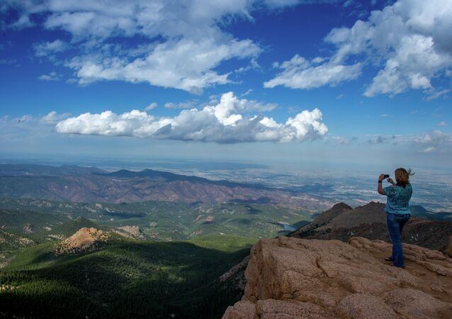 A woman takes a picture at the top of Pikes Peak mountain in the Front Range of the Rocky Mountains within Pike National Forest, 10 miles (16 km) west of Colorado Springs, Colorado, on June 08,2013
