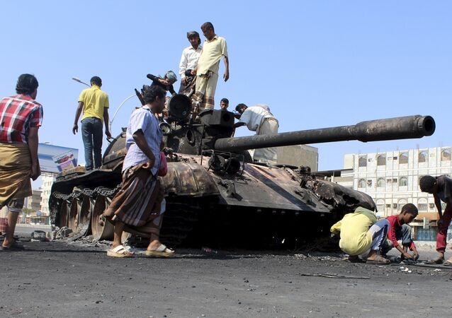 People gather near a tank burnt during clashes on a street in Yemen's southern port city of Aden March 29, 2015
