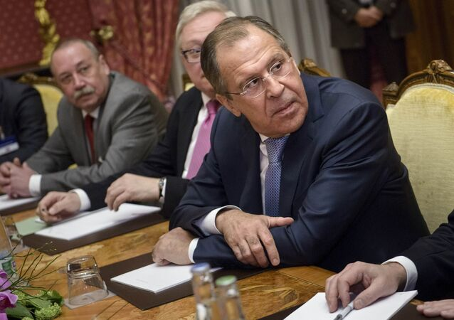 Russian Foreign Minister Sergei Lavrov (R) waits for a meeting with US Secretary of State John Kerry at the Beau Rivage Palace Hotel in Lausanne, Switzerland